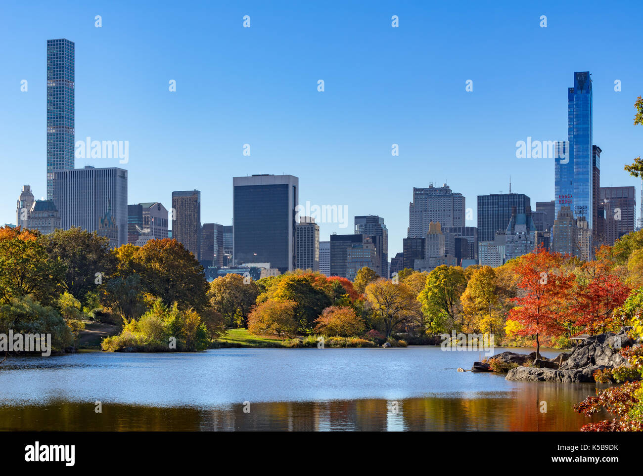 Fallen im Central Park am See mit Midtown Wolkenkratzer. New York City Stockbild