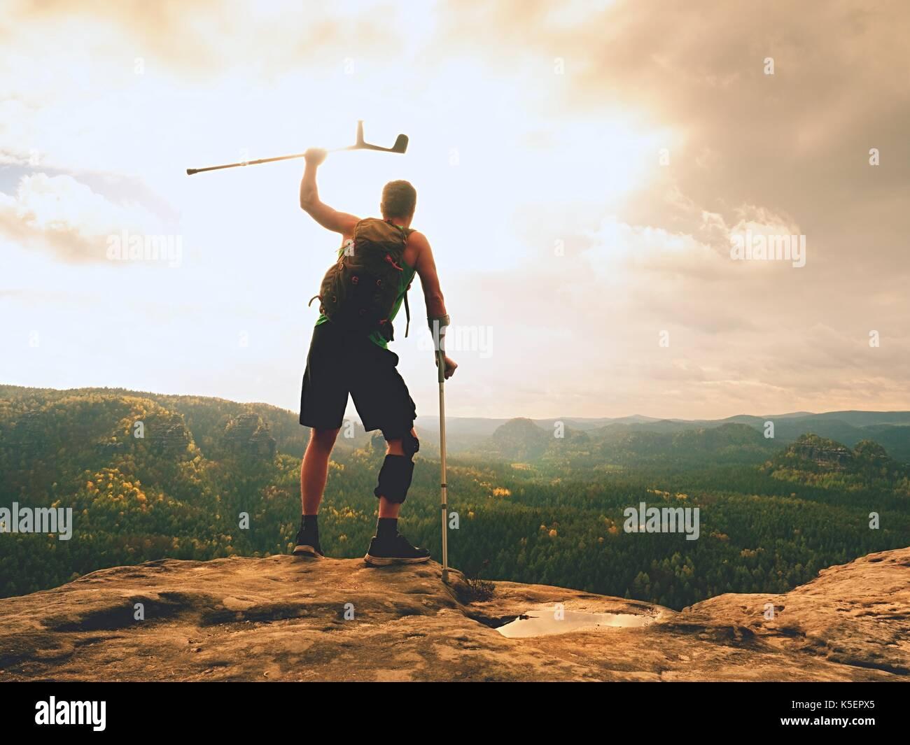 Mann mit Krücken und gebrochenen Bein im Knie fest programmierte Strebe. Reisenden mit verletzten Bein in Bandagen Aufenthalt auf felsigen Sicht in die Berge. Wanderer mit Stockbild