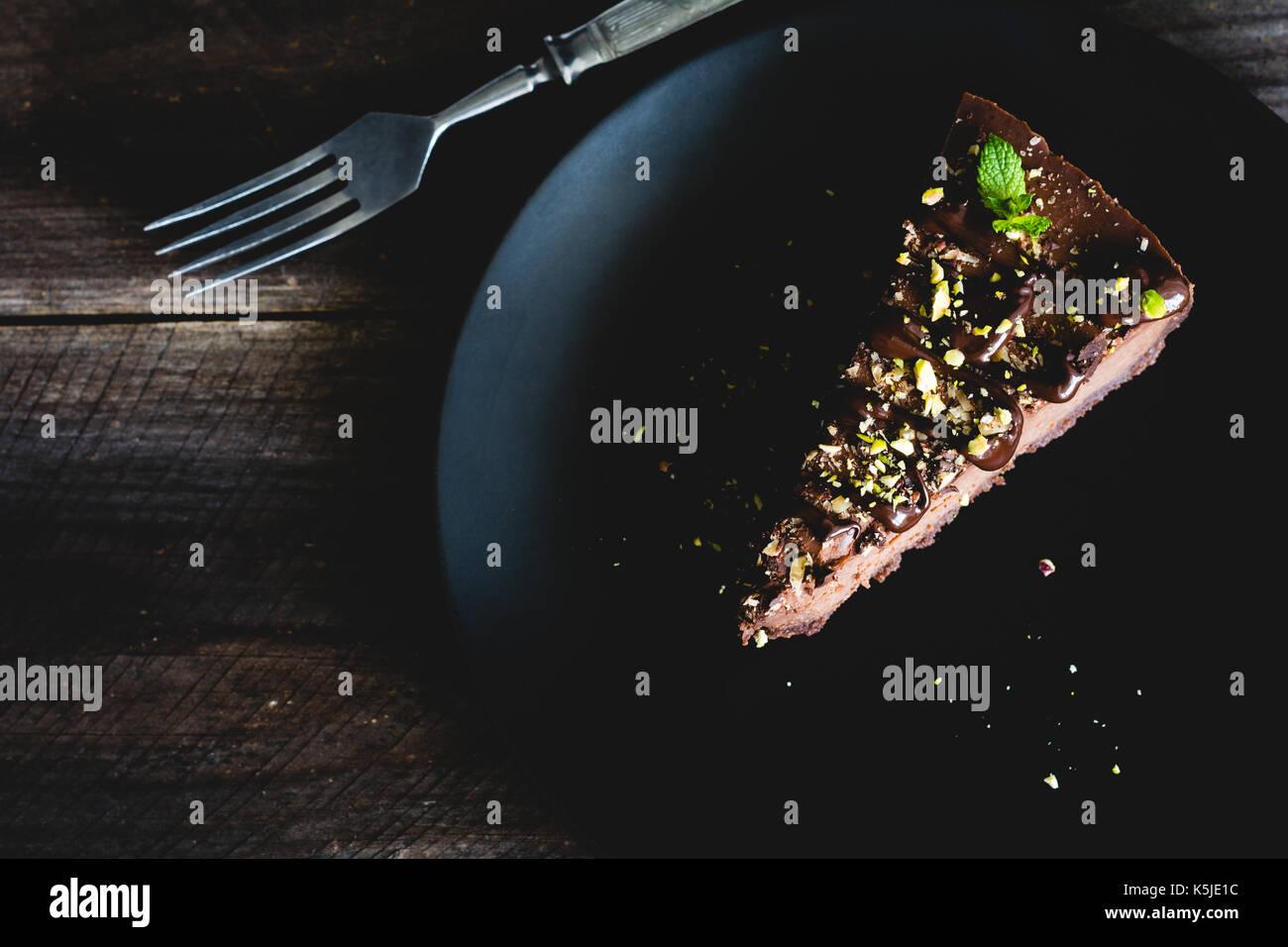 Dunkle Schokolade Käsekuchen mit gehackten Pistazien und minzeblatt auf schwarzem Teller auf hölzernen Tisch eingerichtet. Ansicht von oben, getönten Bild Stockbild