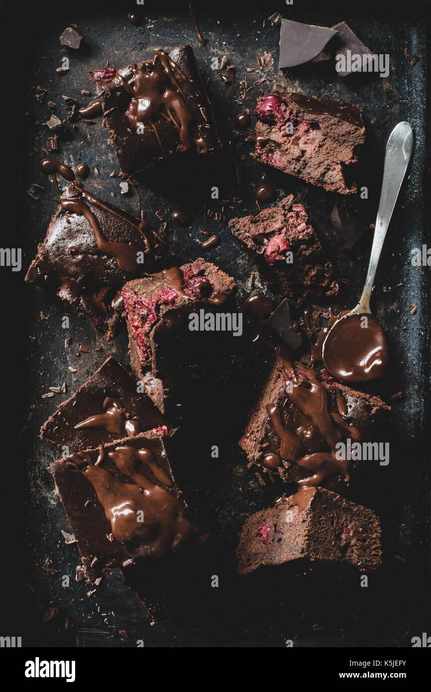 Chocolate Cherry Brownies mit geschmolzener Schokolade auf dunklem Hintergrund eingerichtet. Tabelle Ansicht von oben Stockbild