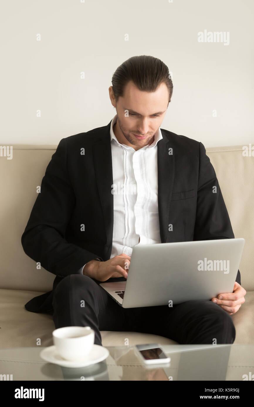 Geschäftsmann auf Laptop fern von zu Hause aus arbeiten. Stockbild