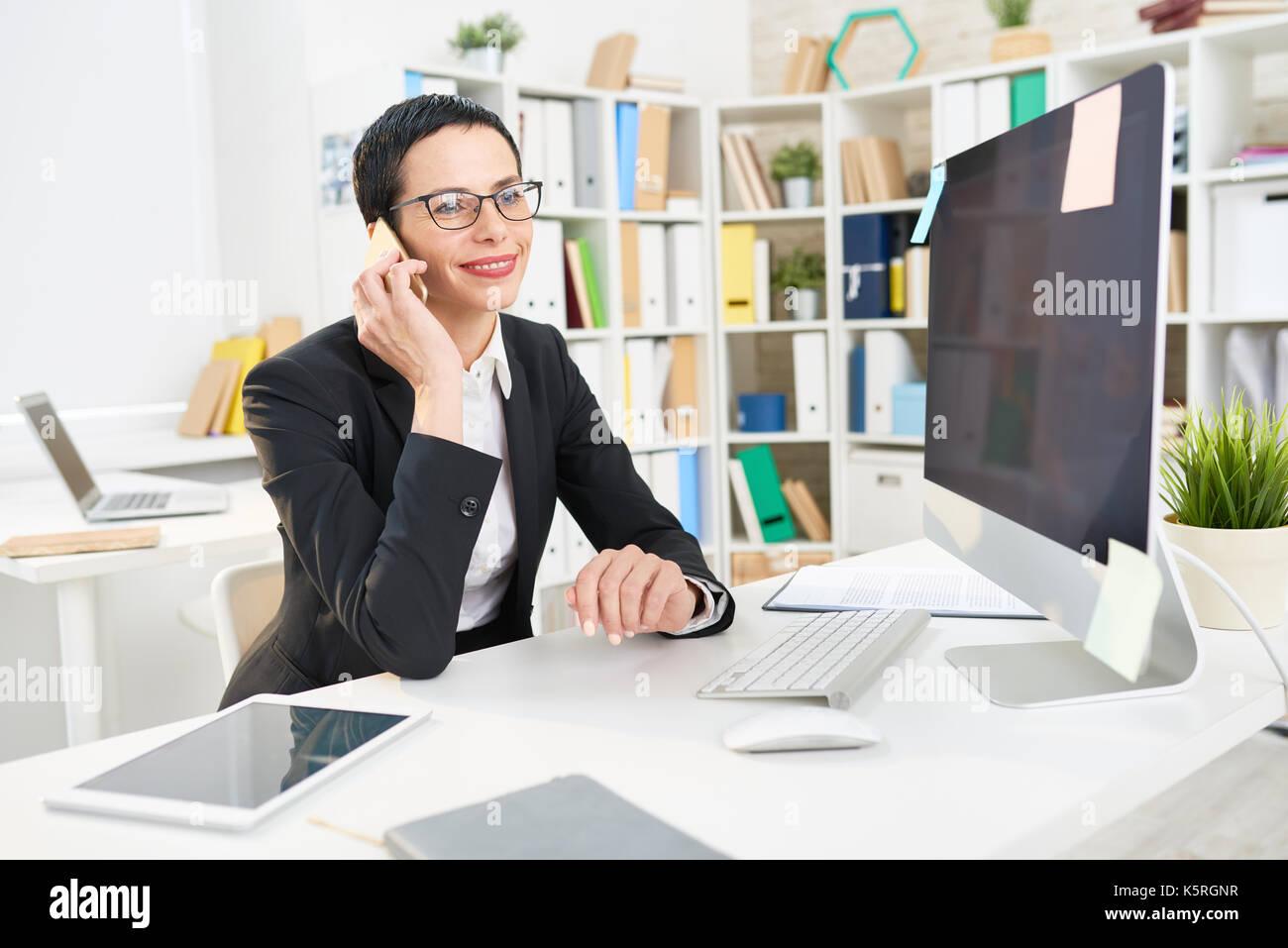 Lächelnd im mittleren Alter Unternehmer sitzen am Schreibtisch ...