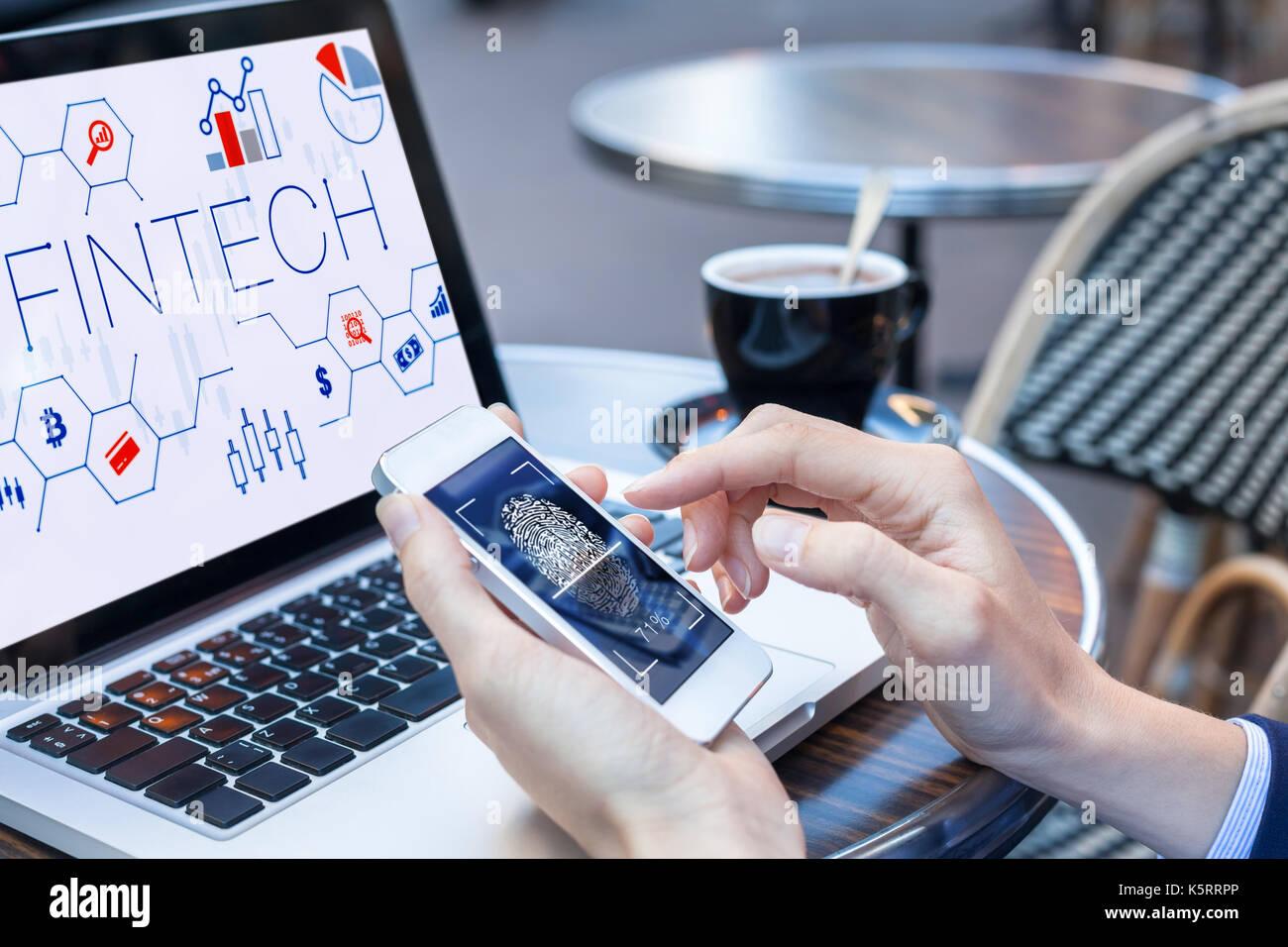 Business Person mittels Fingerabdruck auf dem Smartphone scan sichere Bezahlung im Internet mit Laptop im Hintergrund mit fintech (Zugang zu Finanzierung Stockbild