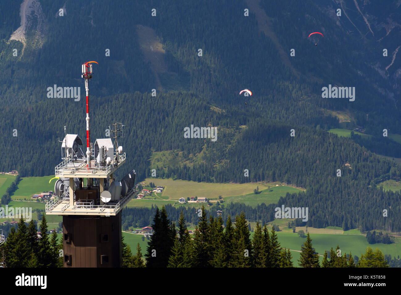 Planai Telekommunikationsturm mit fliegenden Gleitschirme im Hintergrund Stockfoto