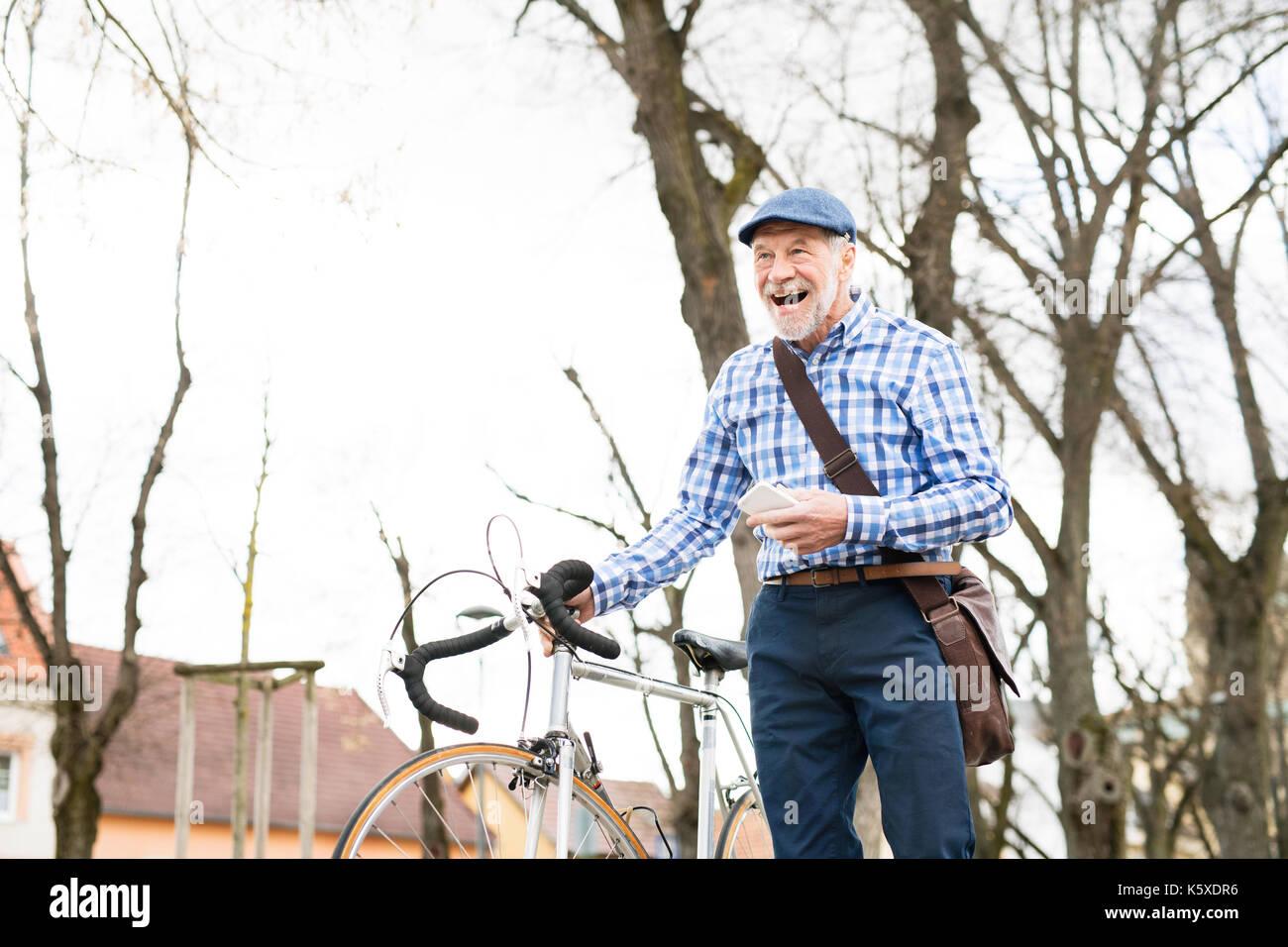 Älterer Mann mit Smartphone und Fahrrad in der Stadt. Stockbild