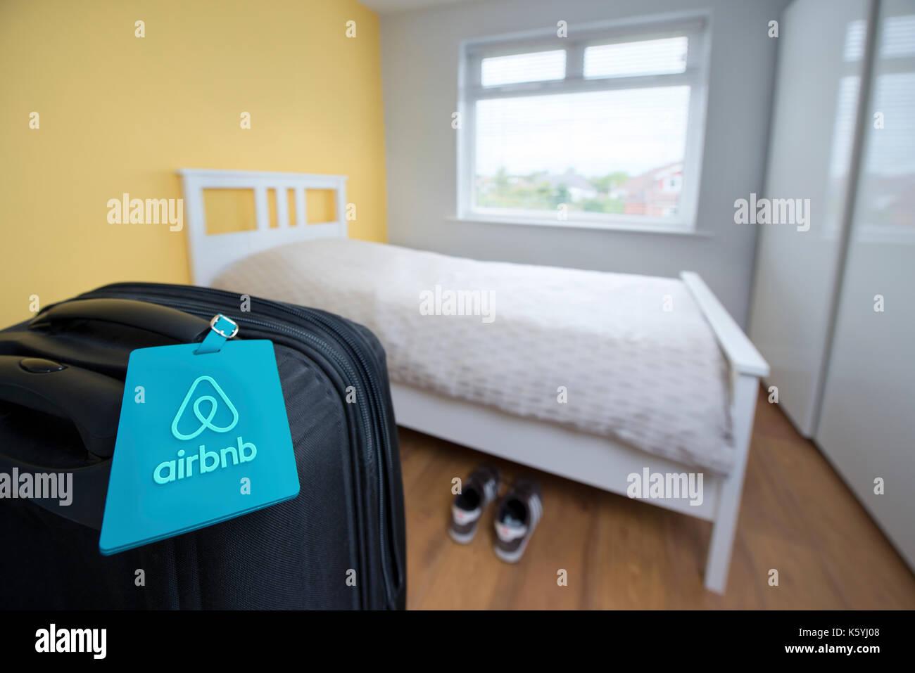 Eine Airbnb branded Kofferanhänger mit einem Koffer in einem Schlafzimmer zur Verfügung als Teil einer Stockbild
