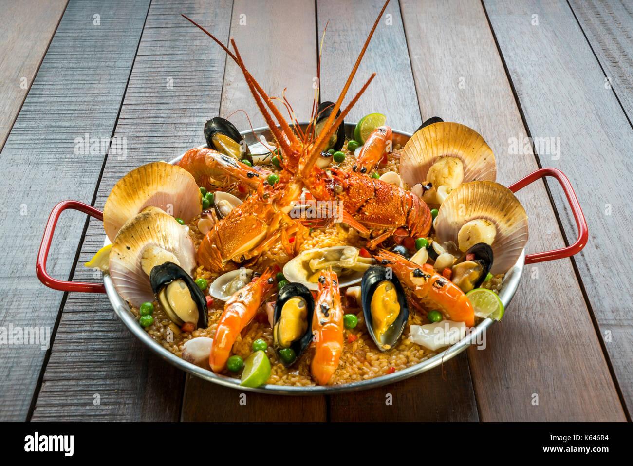 Gourmet Meeresfrüchte Valencia Paella mit frischen Scampi, Muscheln, Muscheln und Tintenfisch auf herzhafte Safran Reis mit Garnelen, scollops, Muscheln und Kalk schichten, Stockbild