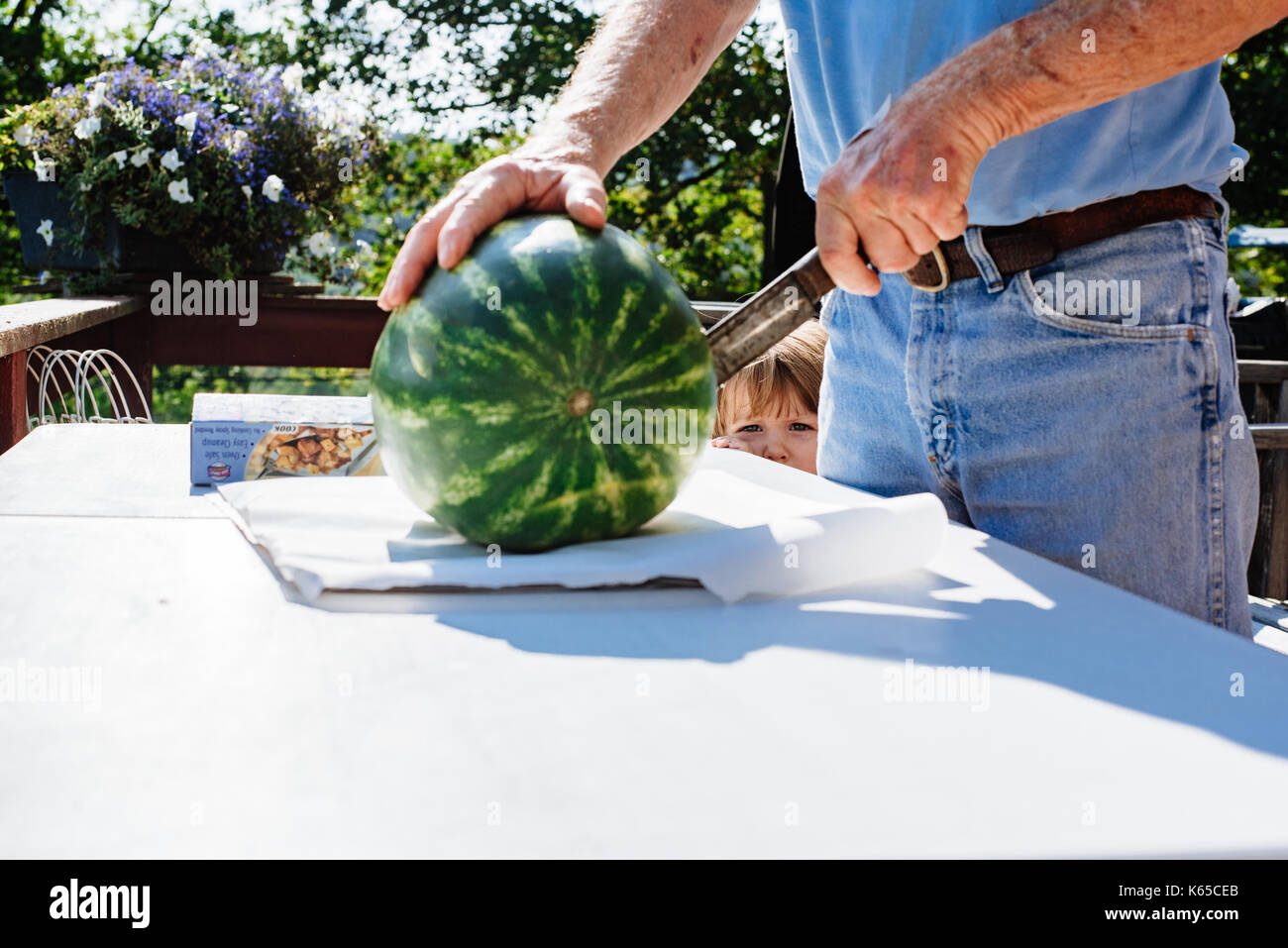 Ein Mann schneidet eine Wassermelone, während ein Kleinkind Uhren. Stockbild