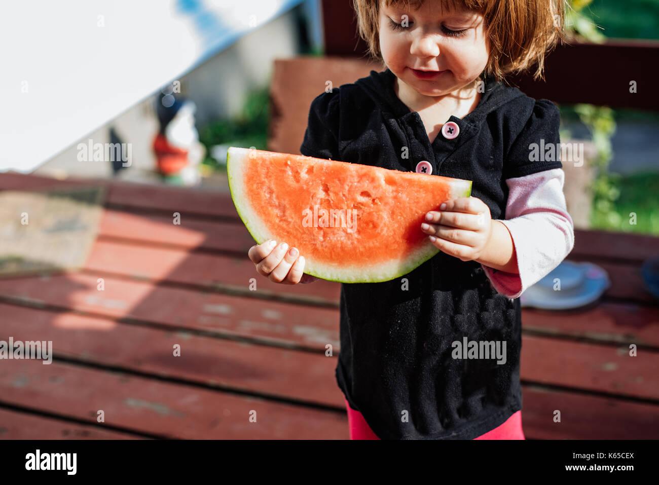 Ein junges Mädchen hält ein Stück Wassermelone an einem warmen Sommertag. Stockbild