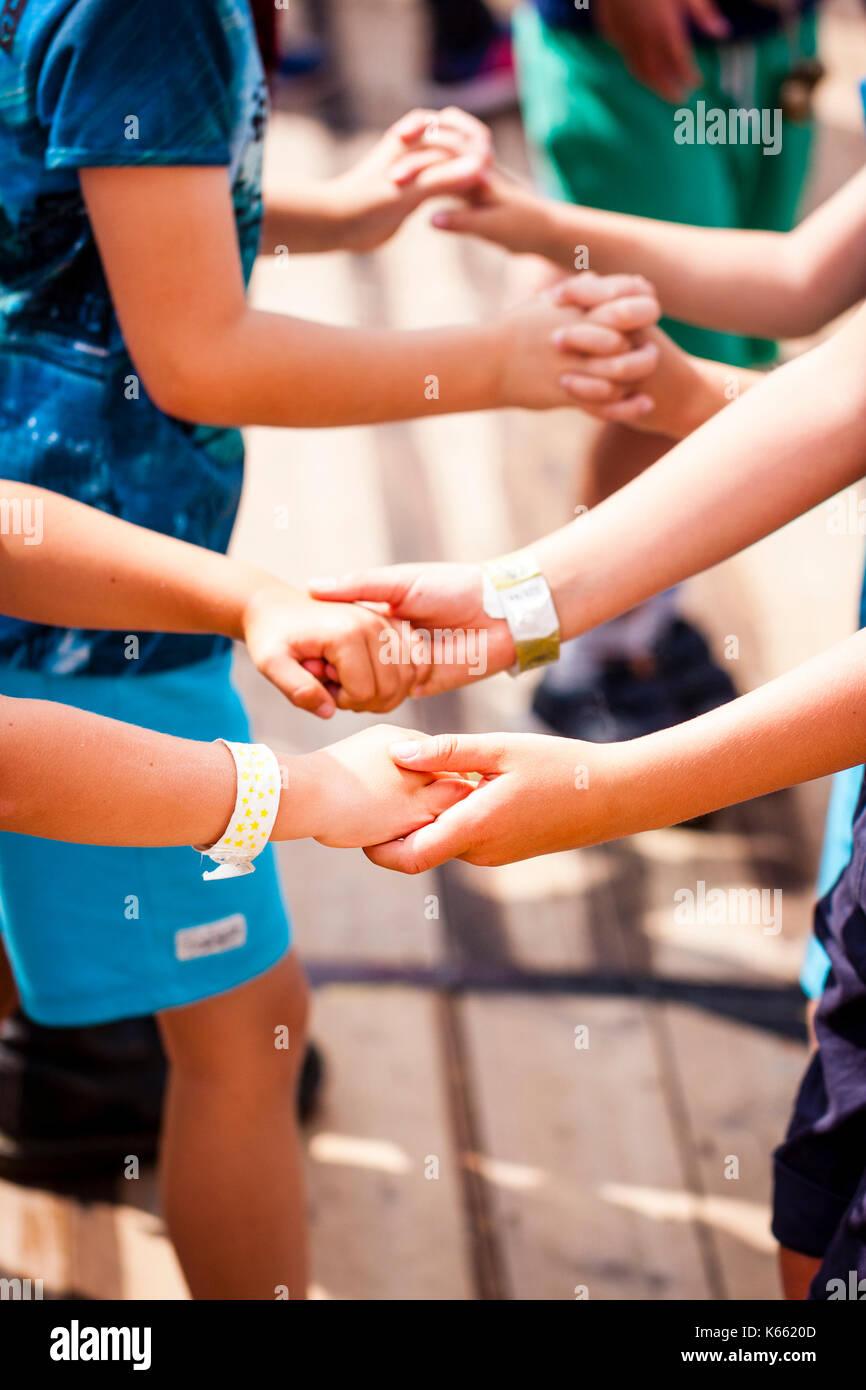 Kinder. Nahaufnahme von Händen und Armen, ein paar Hände halten einander die Hände, das zweite Paar, die Finger ineinander. Zeigen der Freundschaft. Stockbild
