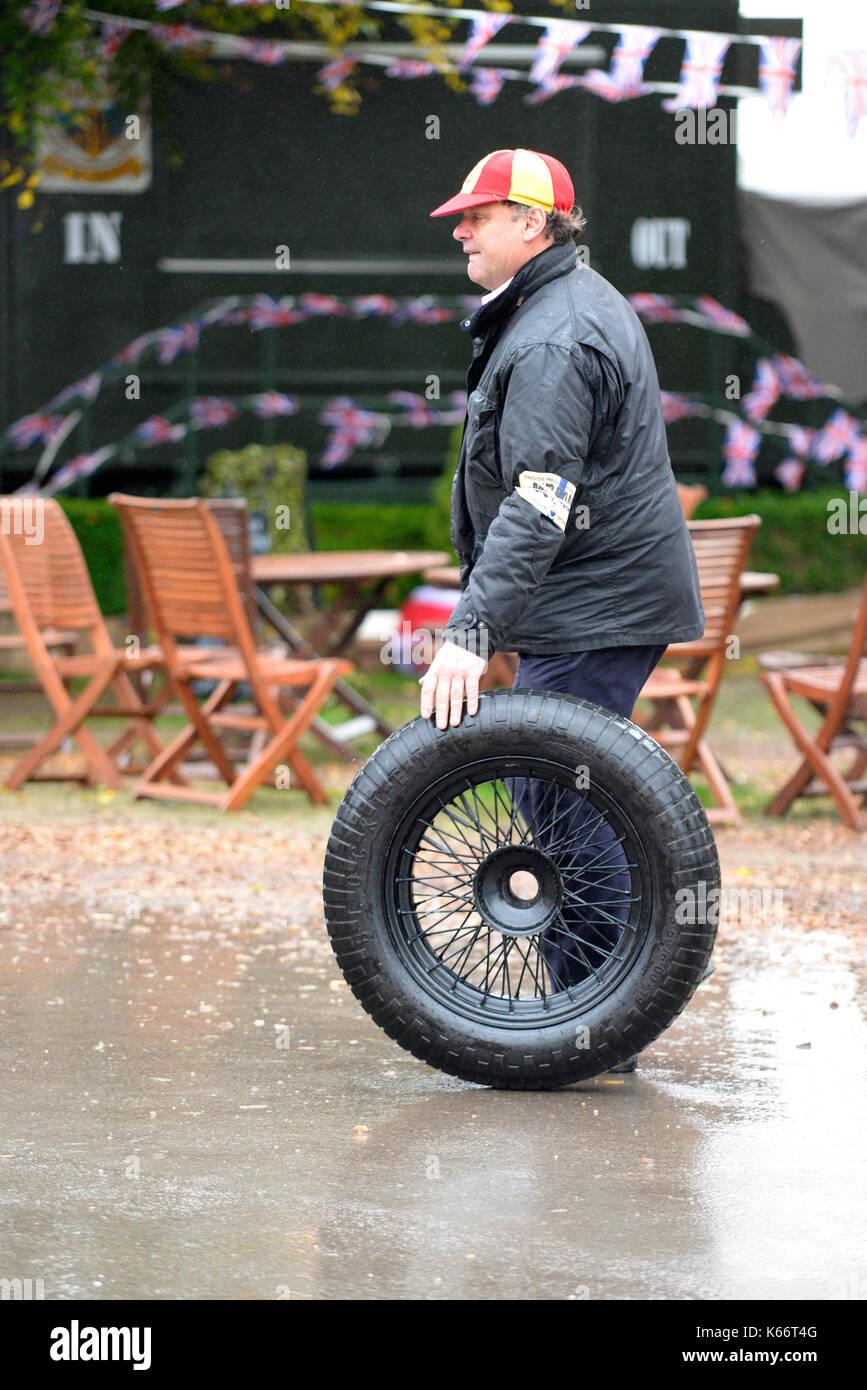 Pit Crew rollt ein Reserverad von den Gruben am Goodwood Revival 2017. Es regnete. Platz für Kopie Stockbild