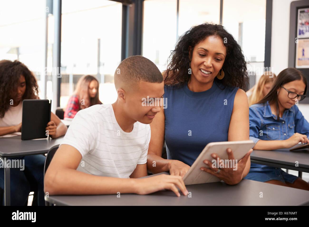 Lehrer helfen Jugendlichen Schüler mit Tablet-PC Stockbild