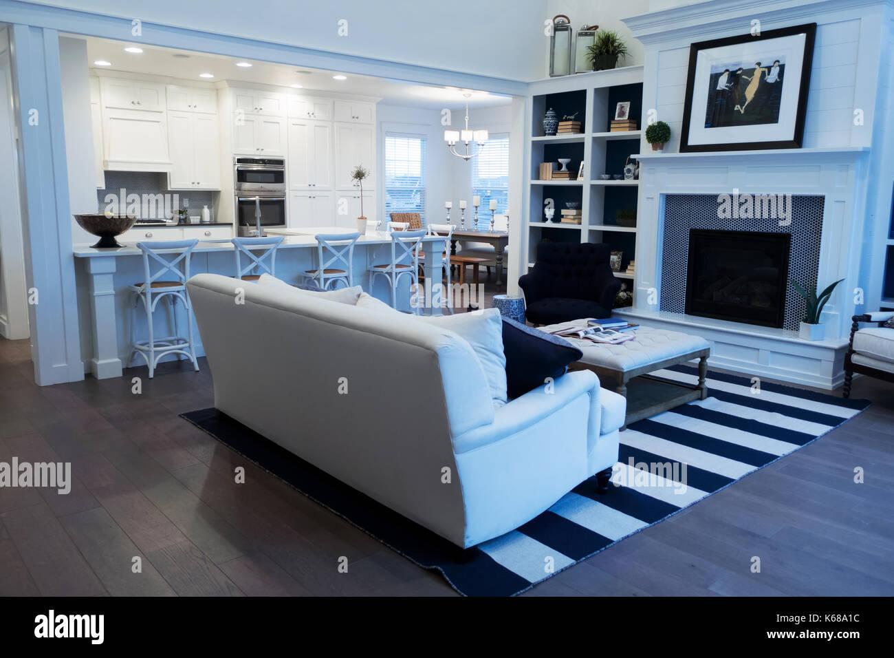 Ein Offenes Wohnzimmer Mit Offener Küche, Eingebaute Bücherregale, Kamin  Und Weißen Couch Suchen.