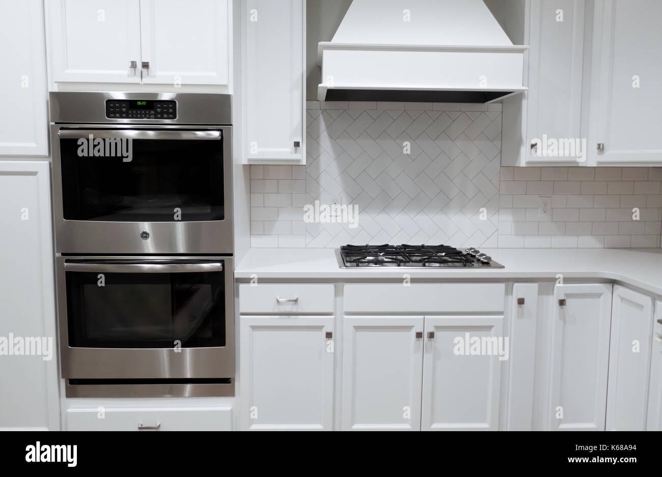 Eine weiße Küche mit Edelstahl Wand, Ofen, Gasherd und ...