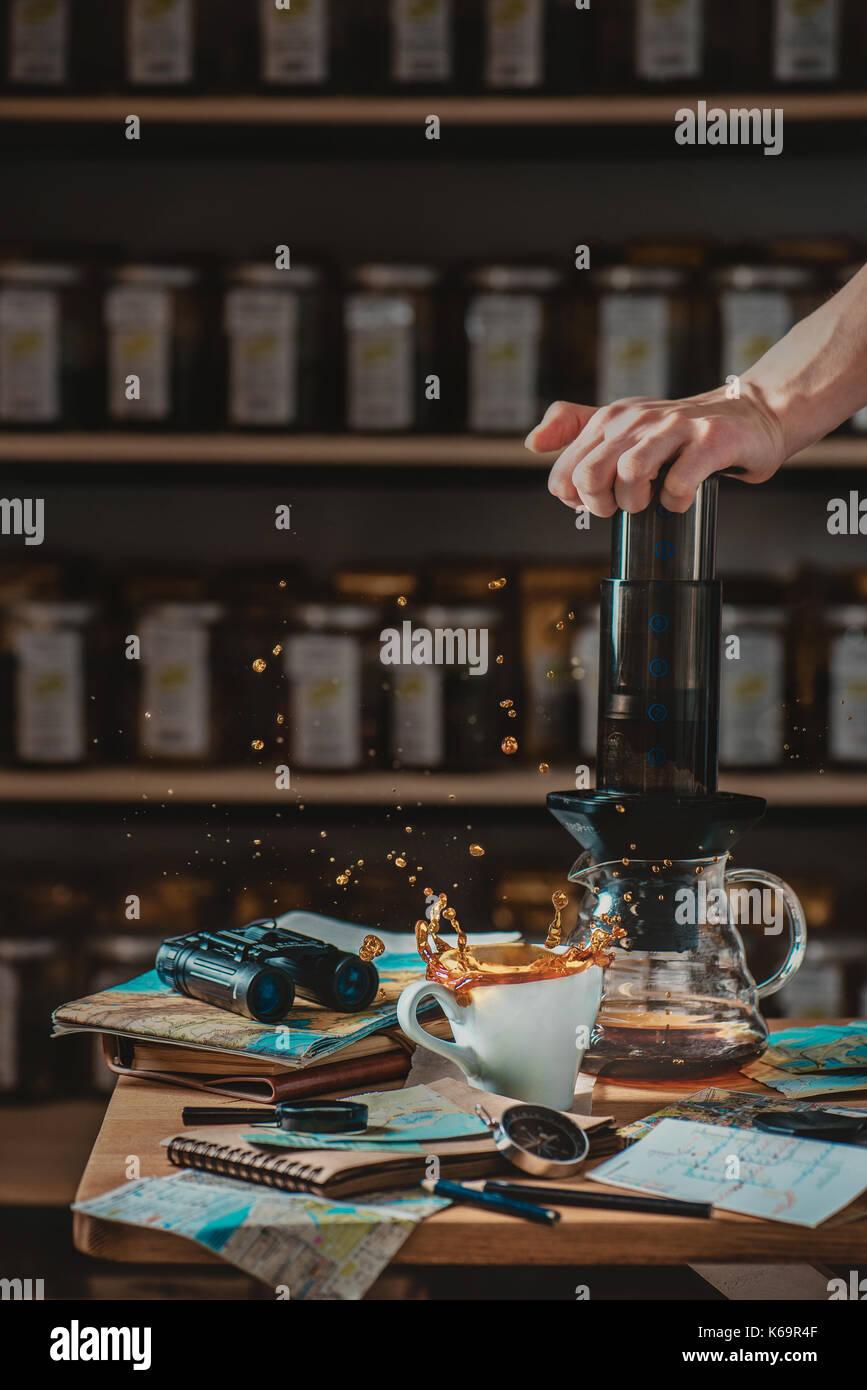 Vorbereitung Kaffee in AeroPress mit einer dynamischen/splash und Stillleben mit Karten und Reisenden Essentials -- Karten, Kompass, Fernglas. Alternative Stockbild