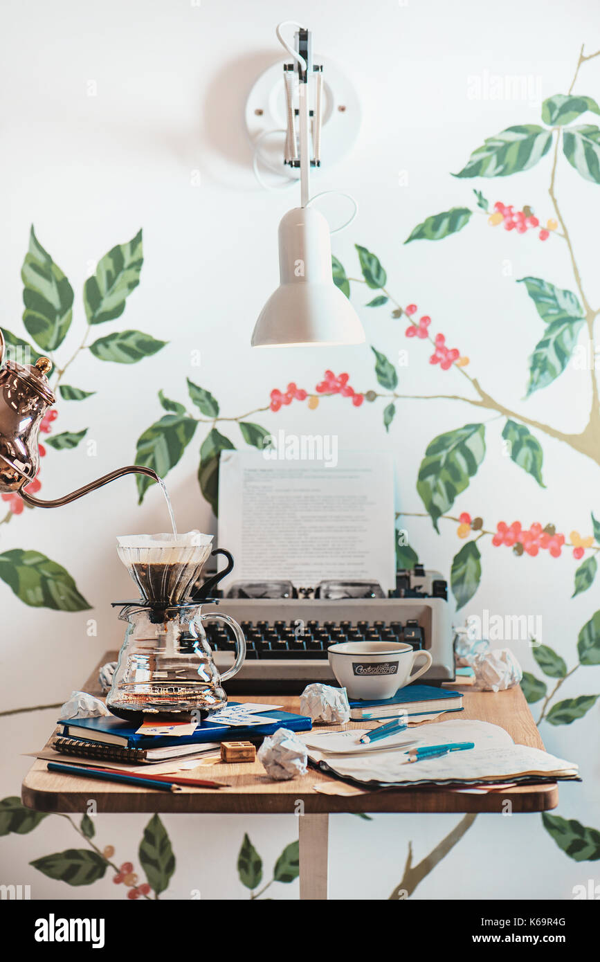 Schriftsteller Arbeitsplatz in einem Cafe mit Schreibmaschine, Entwürfe, zerknittertes Papier und Kaffee, zubereitet mit einer Kegelförmigen gießen Sie über Filter. Alternative/brewi Stockbild