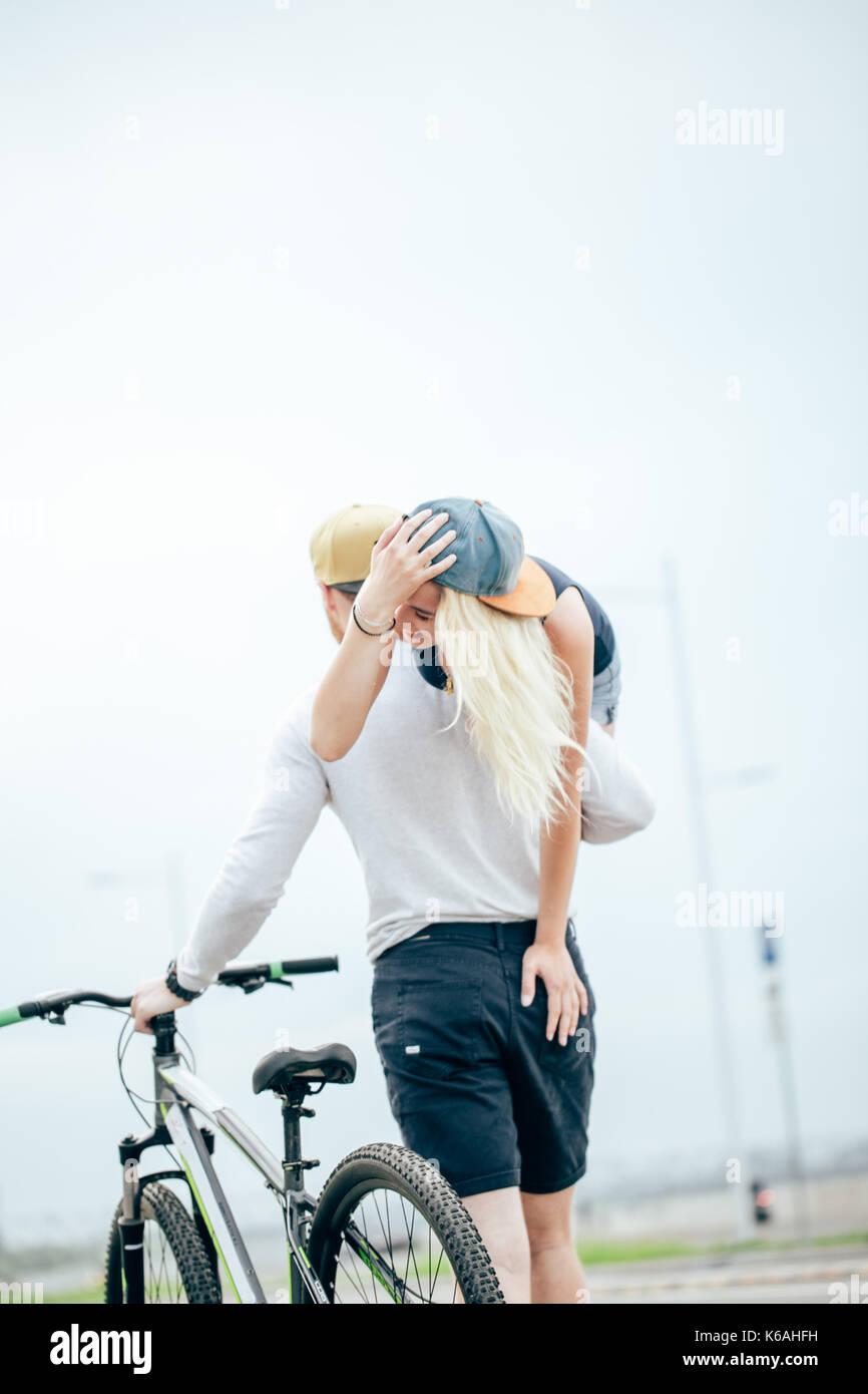 Lächelndes Paar an einem Sommertag, Kerl, der seine Freundin auf der Schulter. Stockbild