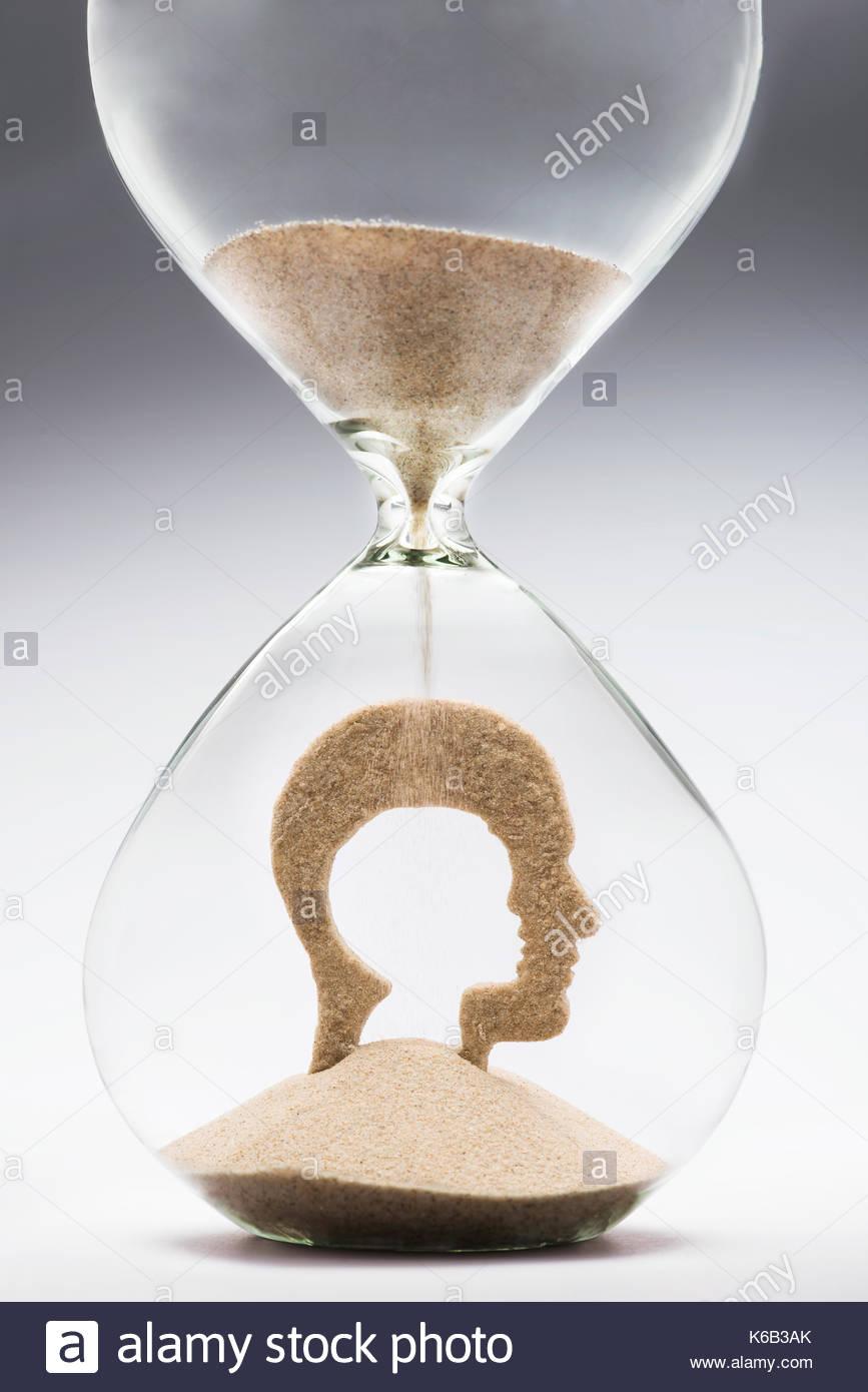 Kindheit Nostalgie Konzept mit fallenden Sand nehmen die Form eines Ausschneiden kind Kopf in ein Mann Kopf, innerhalb einer Sanduhr. Stockbild
