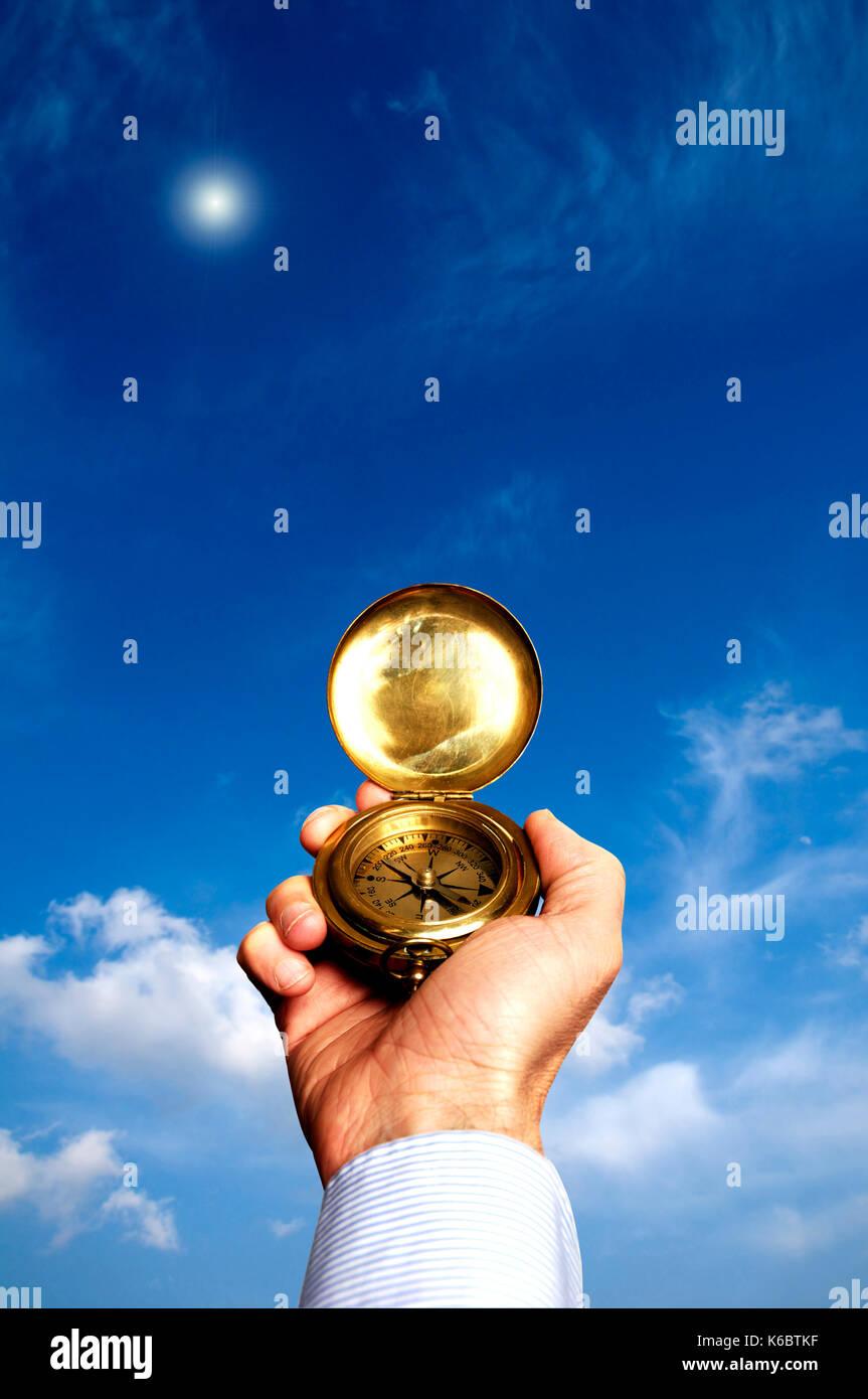 Mann hält einen Kompass, um zu zeigen, in welche Richtung zu nehmen Stockbild