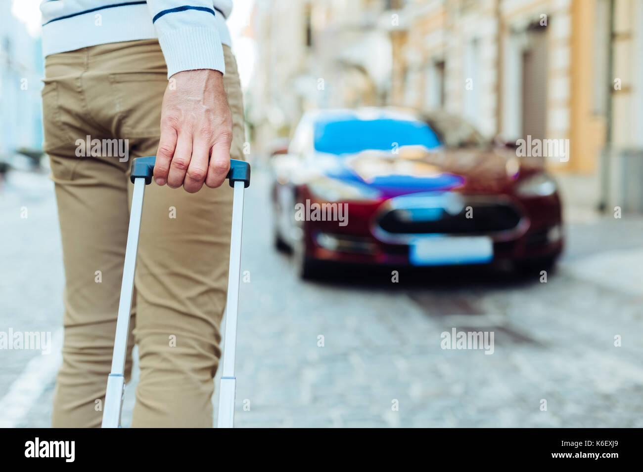 Männliche hand mit einem Koffer Griff Stockbild