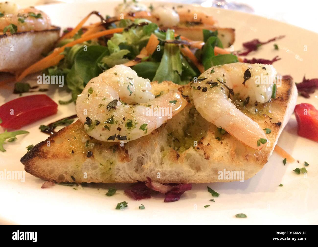 Italienische Vorspeise Bruschetta Con Gamberetti - Marinierte Riesengarnelen mit Knoblauch, Basilikum und Olivenöl auf geröstetem Brot Stockbild