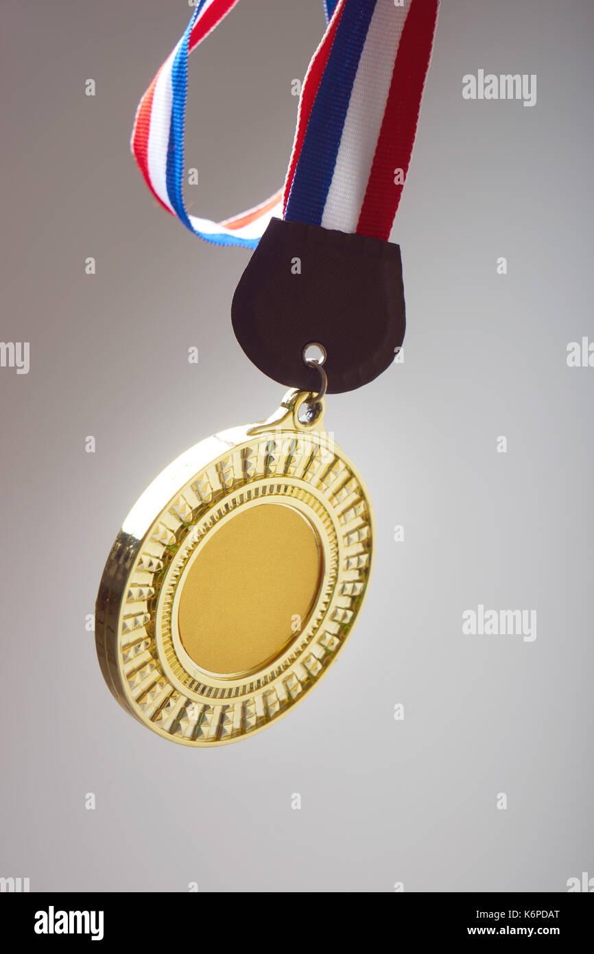 Goldmedaille mit Farbverlauf grau Hintergrund isolieren. Stockbild