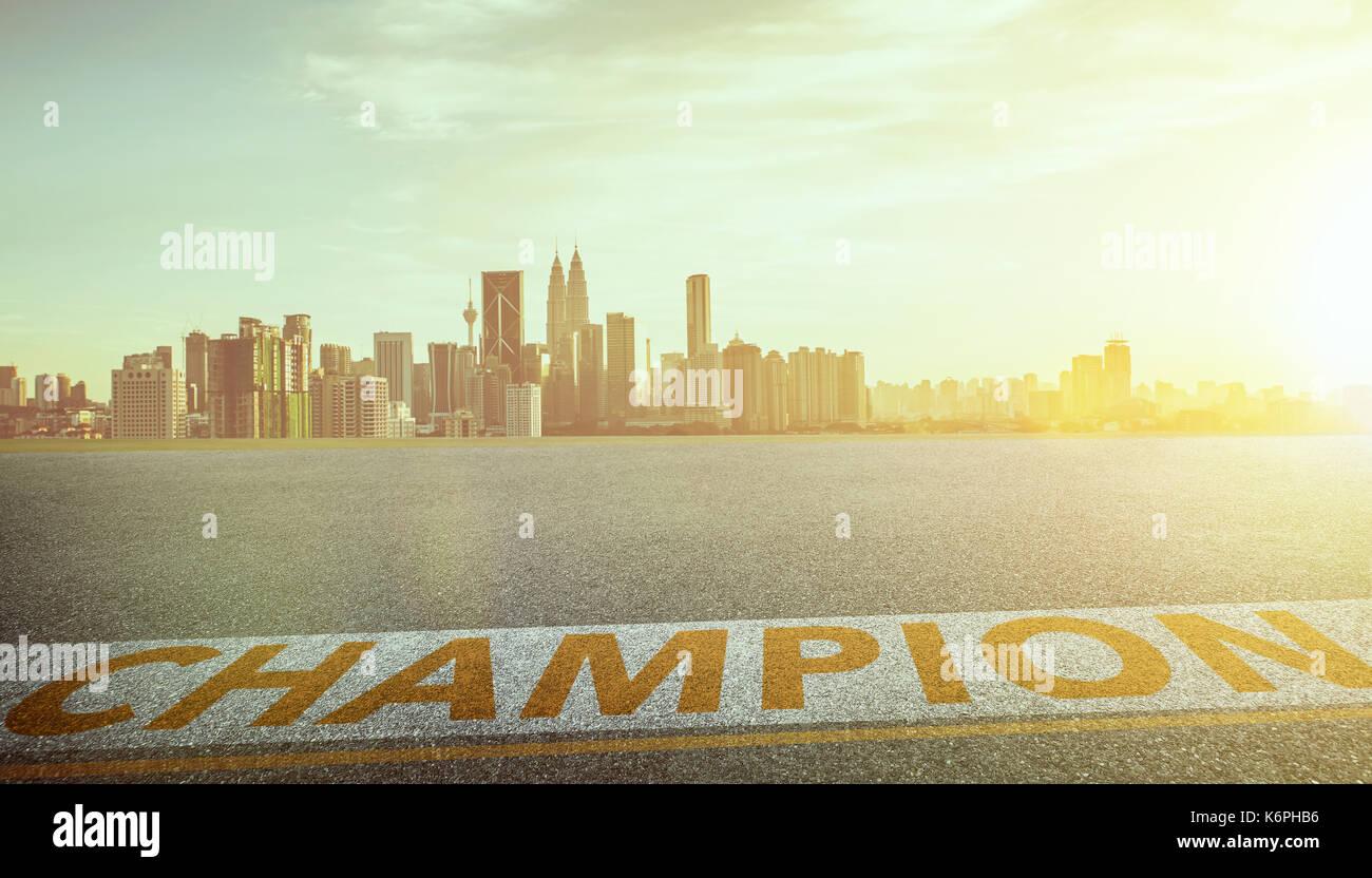 Blick auf den leeren Asphalt mit Champion Wort und die Skyline der Stadt. Abend Szene. Stockbild