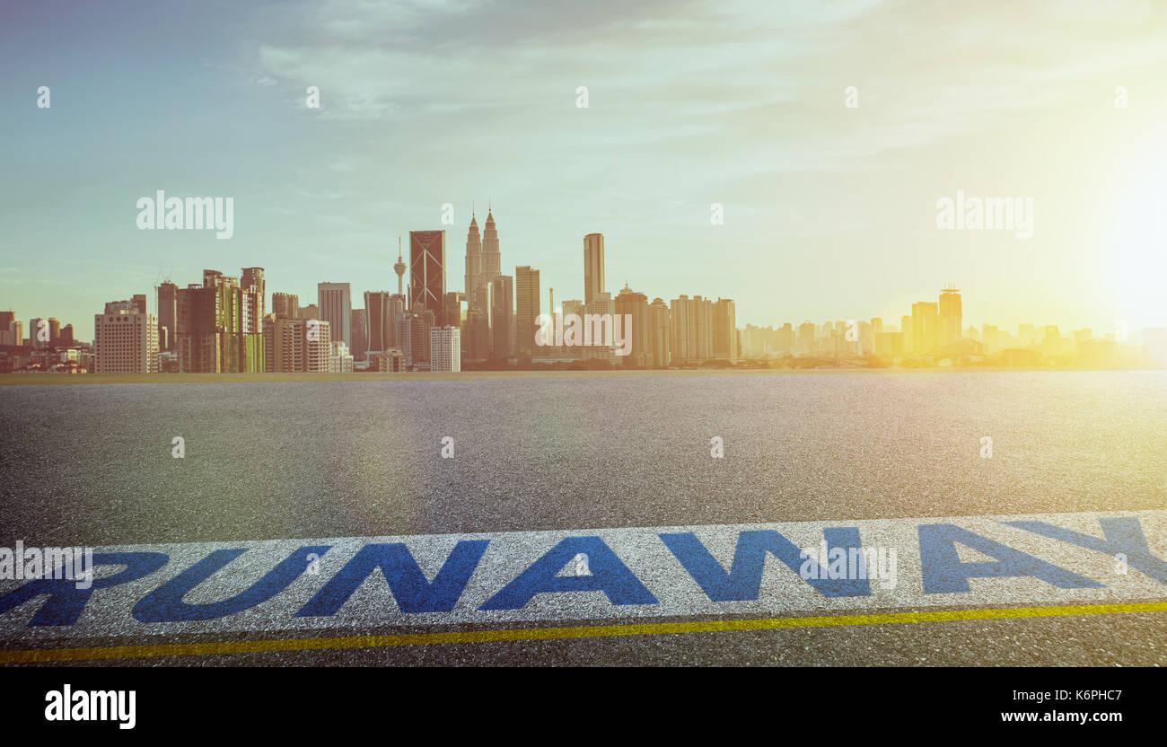 Blick auf den leeren Asphalt mit runaway Wort und die Skyline der Stadt. Abend Szene. Stockbild