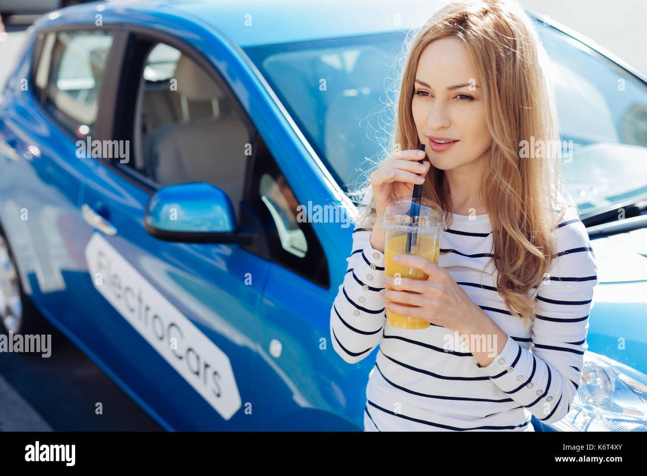 Freudige schöne Frau trinkt Orangensaft Stockbild