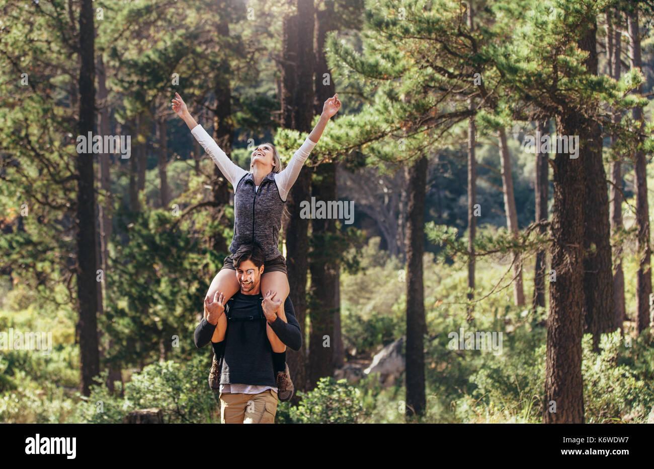 Wandern paar Spaß beim Wandern im Wald. Frau reiten Huckepack auf Mann mit Armen beim Wandern im Wald gespannt. Stockbild