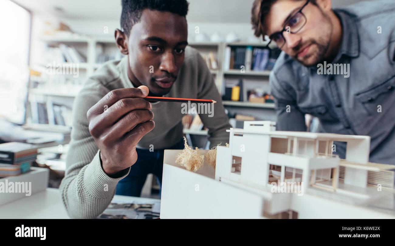Zwei männliche Architekten im Büro diskutieren Bauvorhaben. Die jungen Männer arbeiten gemeinsam Stockbild