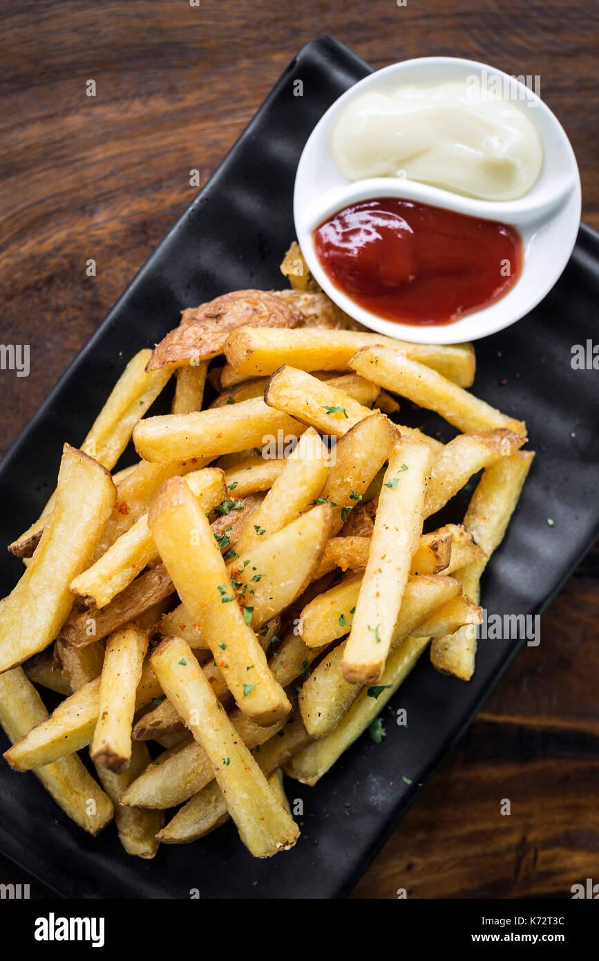 Pommes Chips Snack mit diping Soßen auf hölzernen Tisch Stockbild