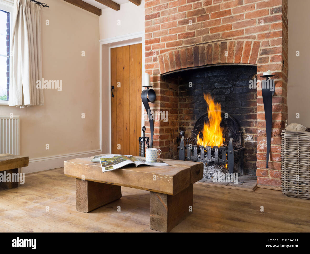 Ein Loderndes Feuer In Einem Roten Backstein Kamin Im Wohnzimmer Ein  Landhaus Mit Chunky Rustikalen Möbeln