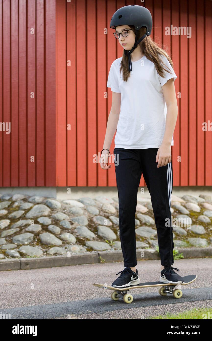 Junges Mädchen mit schützenden skateboard Helm skateboarding im Freien Model Release: Ja. Property Release: Nein. Stockbild