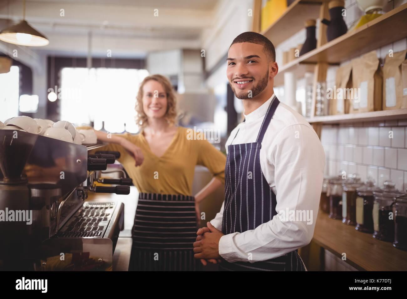 Portrait von lächelnden jungen Kellner und Kellnerinnen stehen durch die espressomaschine im Coffee Shop Stockfoto