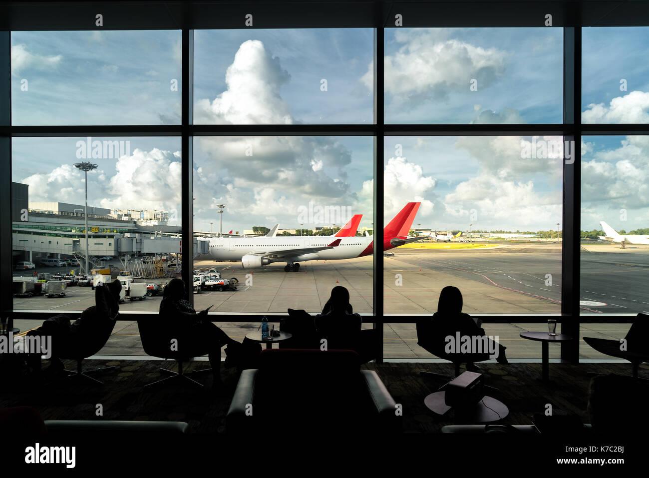 Silhouette der Passagier warten Flug für Reisen in Lounge am Flughafen Terminal. Innenraum Flughafen. Stockbild