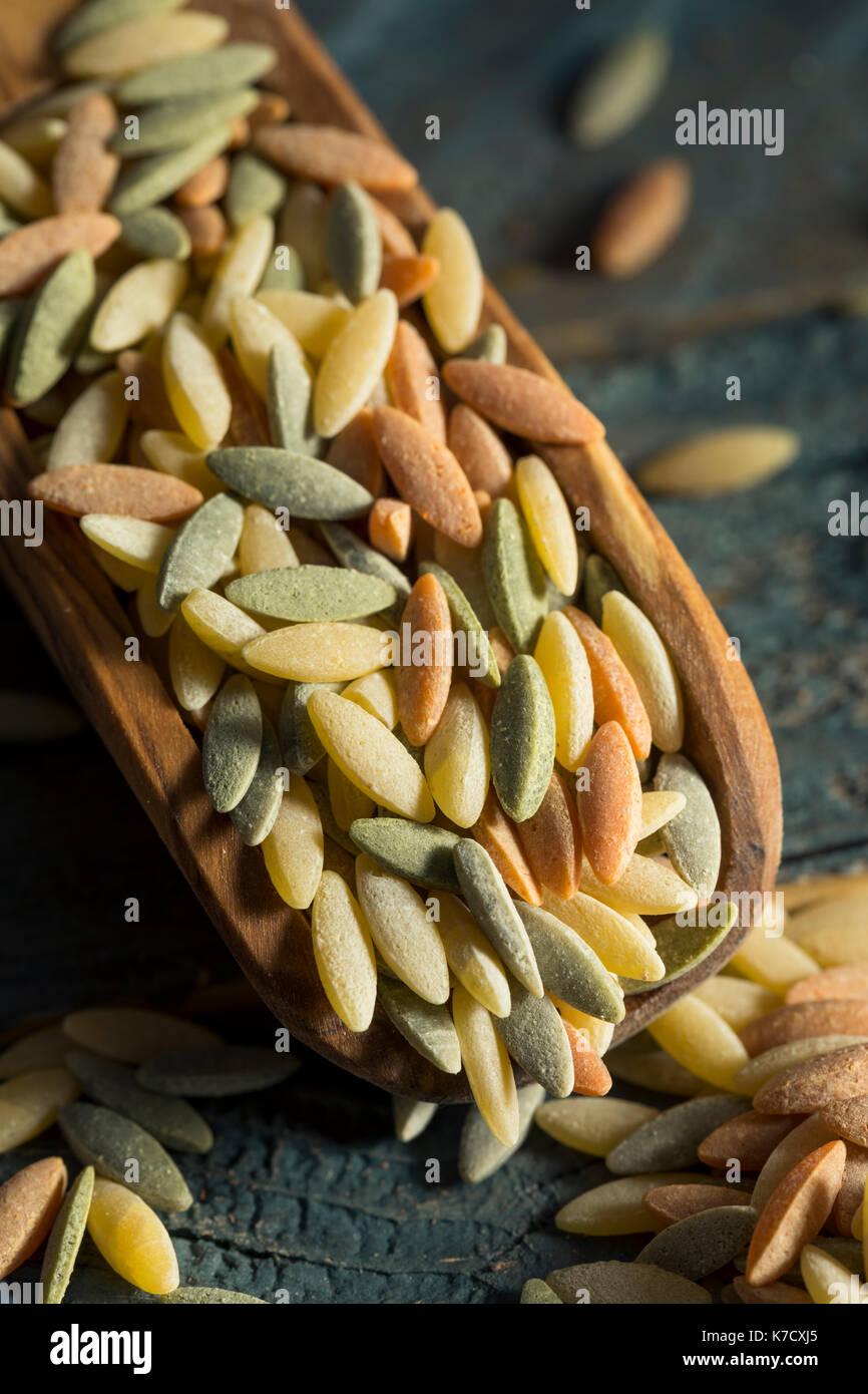 Trockene organische Tricolor Orzo Pasta in eine Schüssel geben. Stockbild