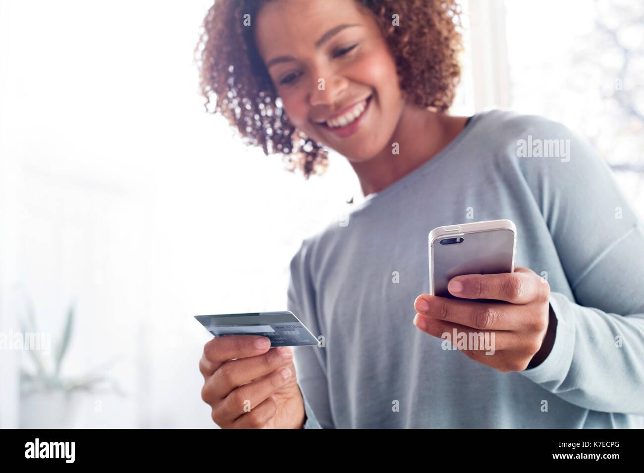 Mitte der erwachsenen Frau mit Kreditkarte und Handy. Stockbild