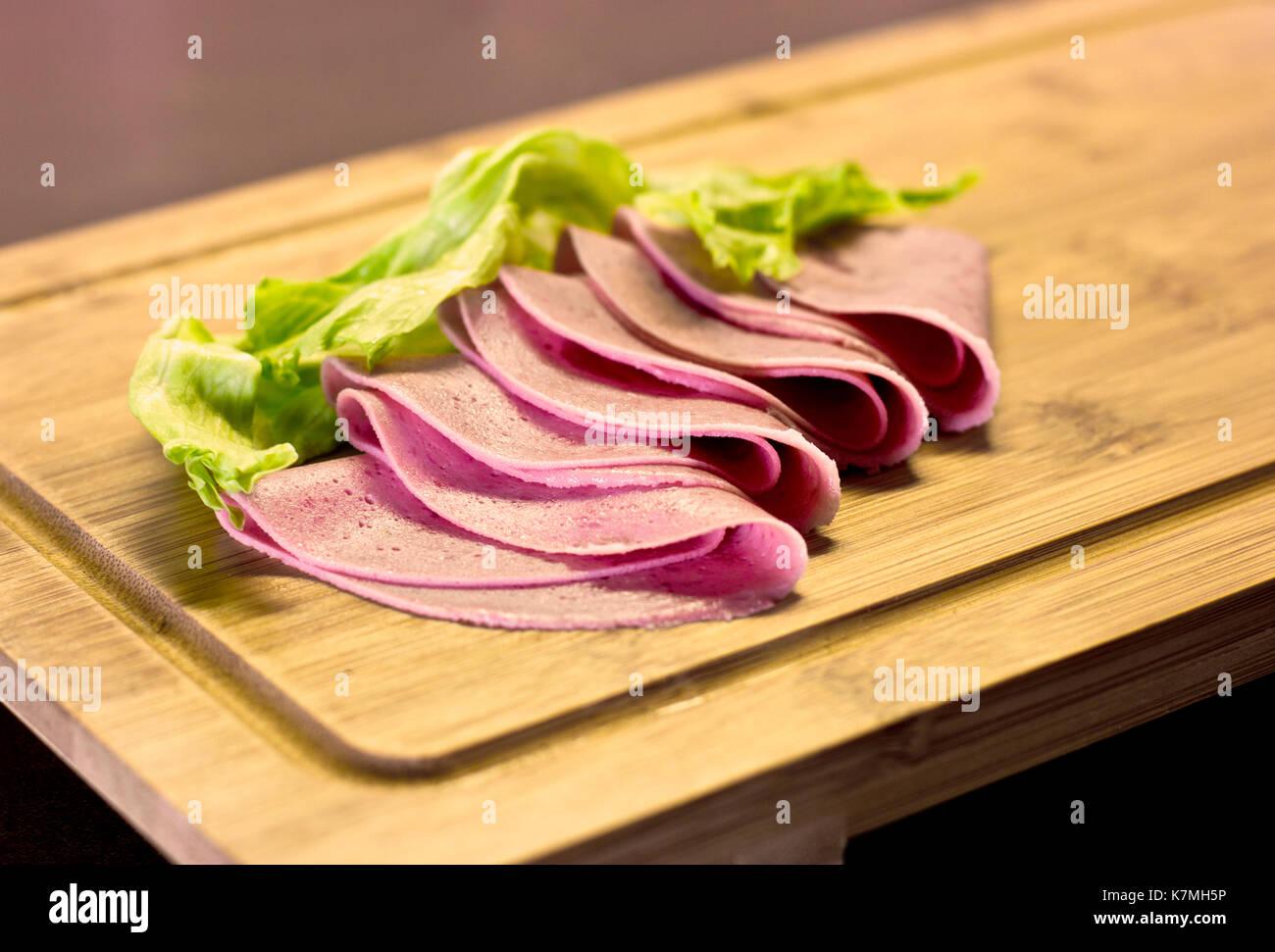Dünn geschnittene Wurst mit grünem Salat auf Holzbrett Stockbild