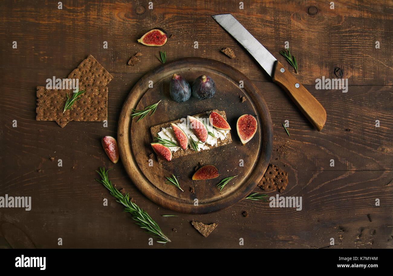 Kleine Laib Brot und Kuchen Käse, Feigen und Rosmarin auf dem Tisch Stockbild