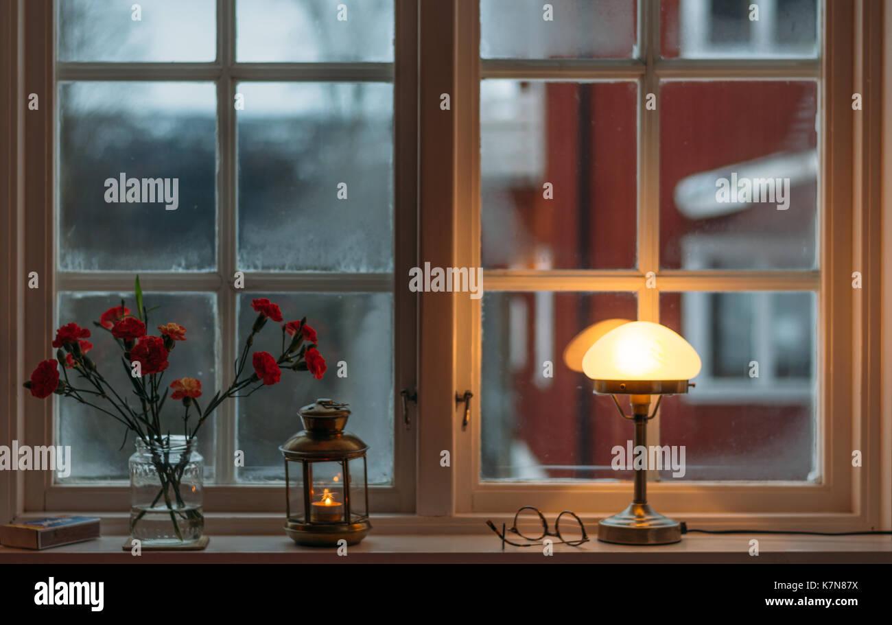 Blick vom gemütlichen Fenster mit Lampe und Blumen Stockbild
