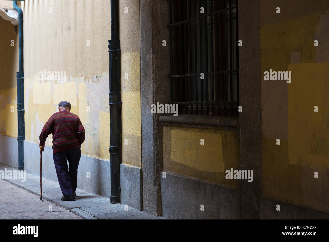 Alter Mann mit Walking Kranken und tragen cap Bummeln in der Altstadt von Avila, Spanien Stockbild