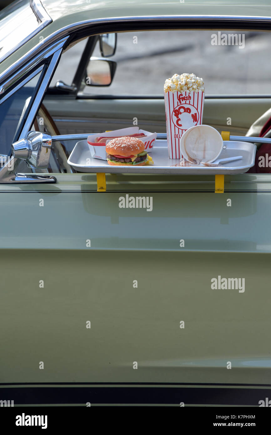 Ein Beef Burger und Pommes an die Tür eines klassischen Amerikanischen Auto auf eine Fahrt durch Gerichte zum Stockbild