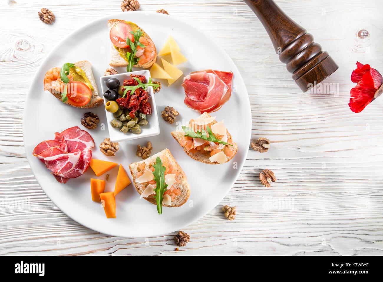 Auswahl an leckeren Bruschetta oder Häppchen auf taosted Baguette und Quark Käse garniert mit geräuchertem Lachs, Garnelen. Stockbild