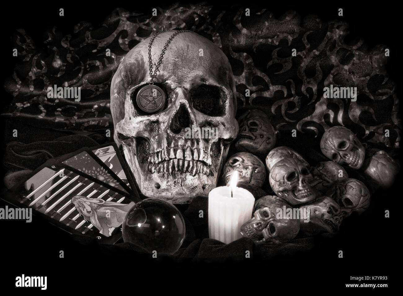 Schädel mit okkulten Utensilien, crystal ball, Tarot Karten, ein silbernes Pentagramm, in retro Schwarz und Weiß Stockbild