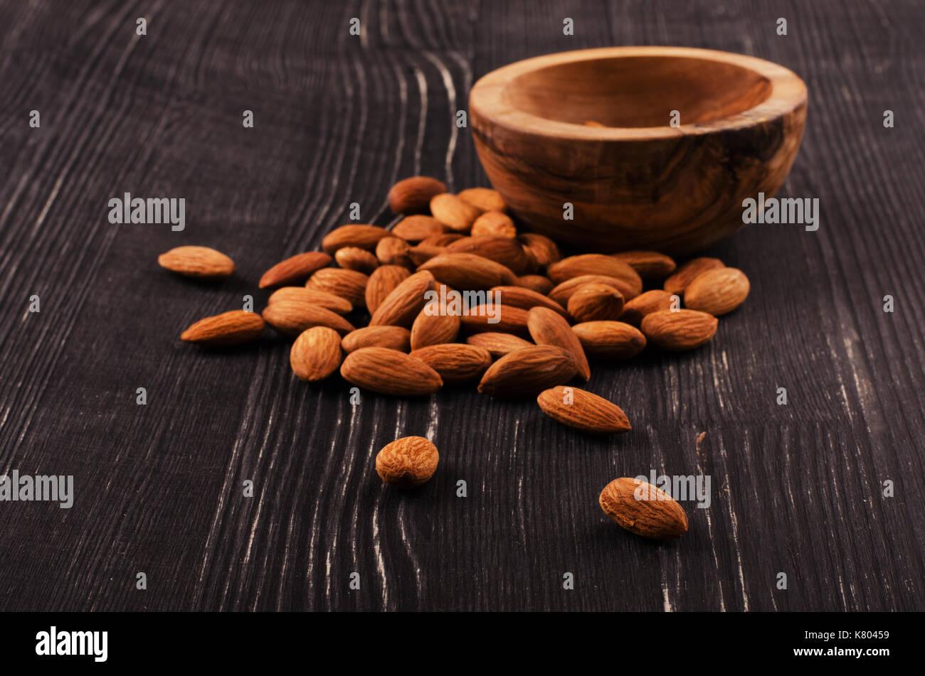 Mandeln in brauner Schale auf Holz- Hintergrund Stockbild