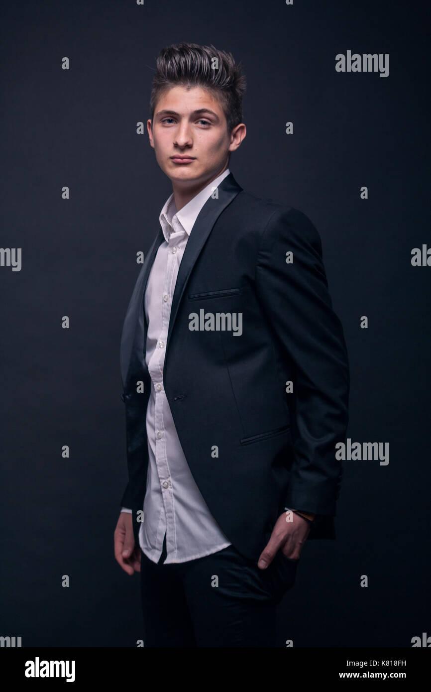 Ein junger Teenager, schwarzer Hintergrund, Studio, trägt Anzug jacke Shirt, Oberkörper Stockbild