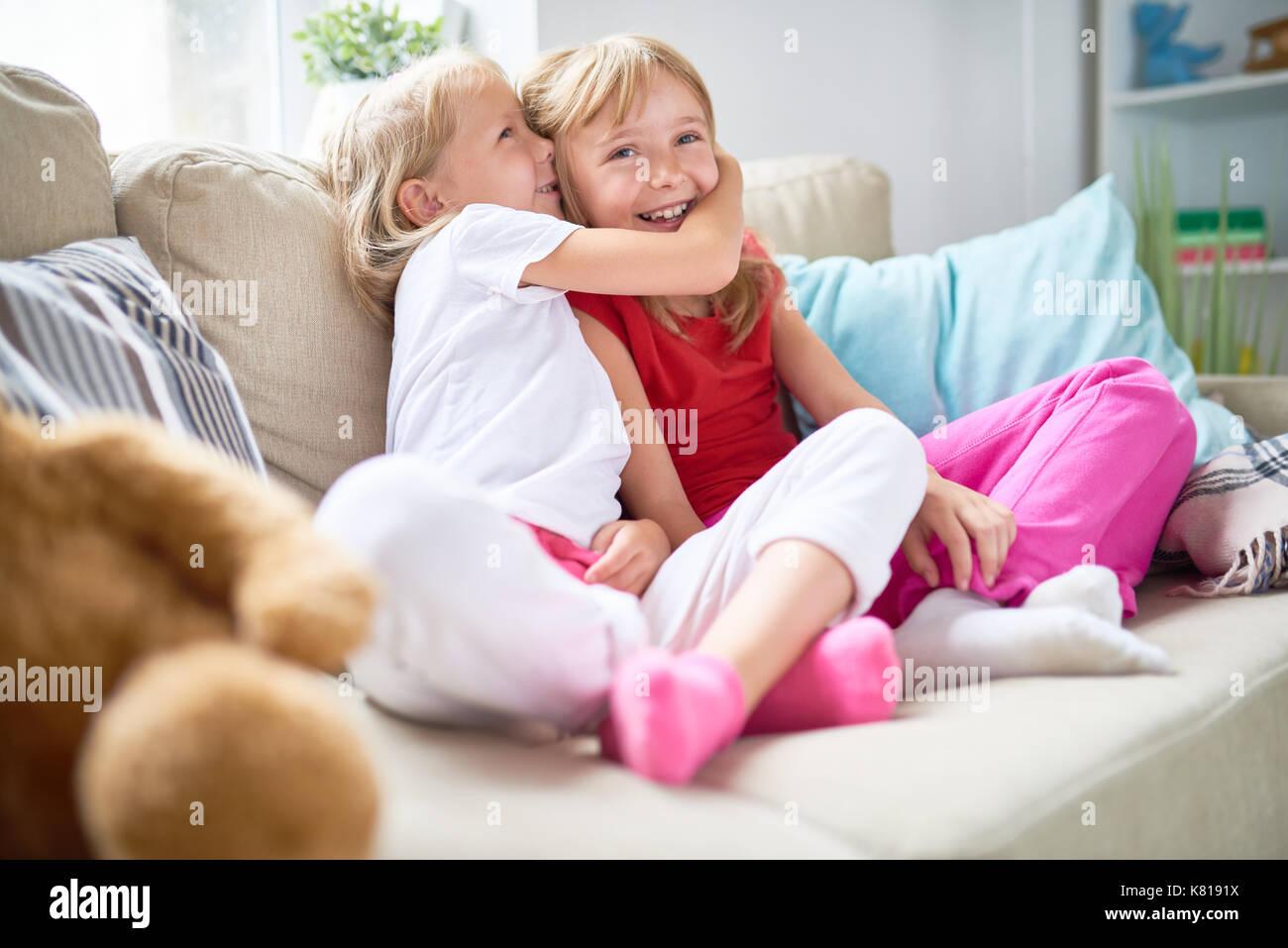 Süße blonde Mädchen im Geheimen mit ihrem Lächeln ältere Schwester beim verbringen Wochenende zusammen im gemütlichen Wohnzimmer Stockbild