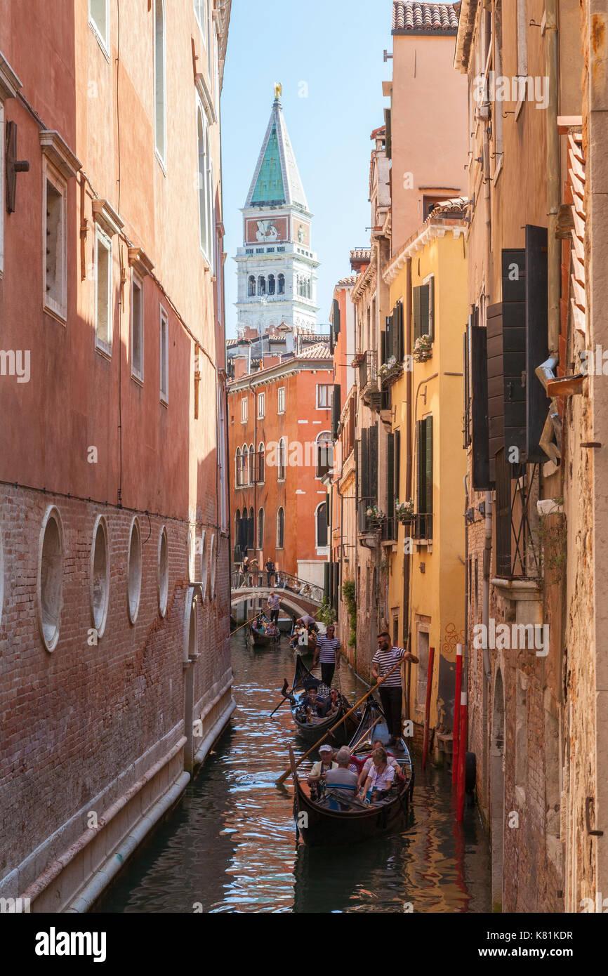Die Gondolieri rudern Gondeln durch einen sehr schmalen Kanal, in San Marco, Venedig, Italien mit dem Campanile von San Marco Basilika hinter Ihnen aus gesehen Stockbild