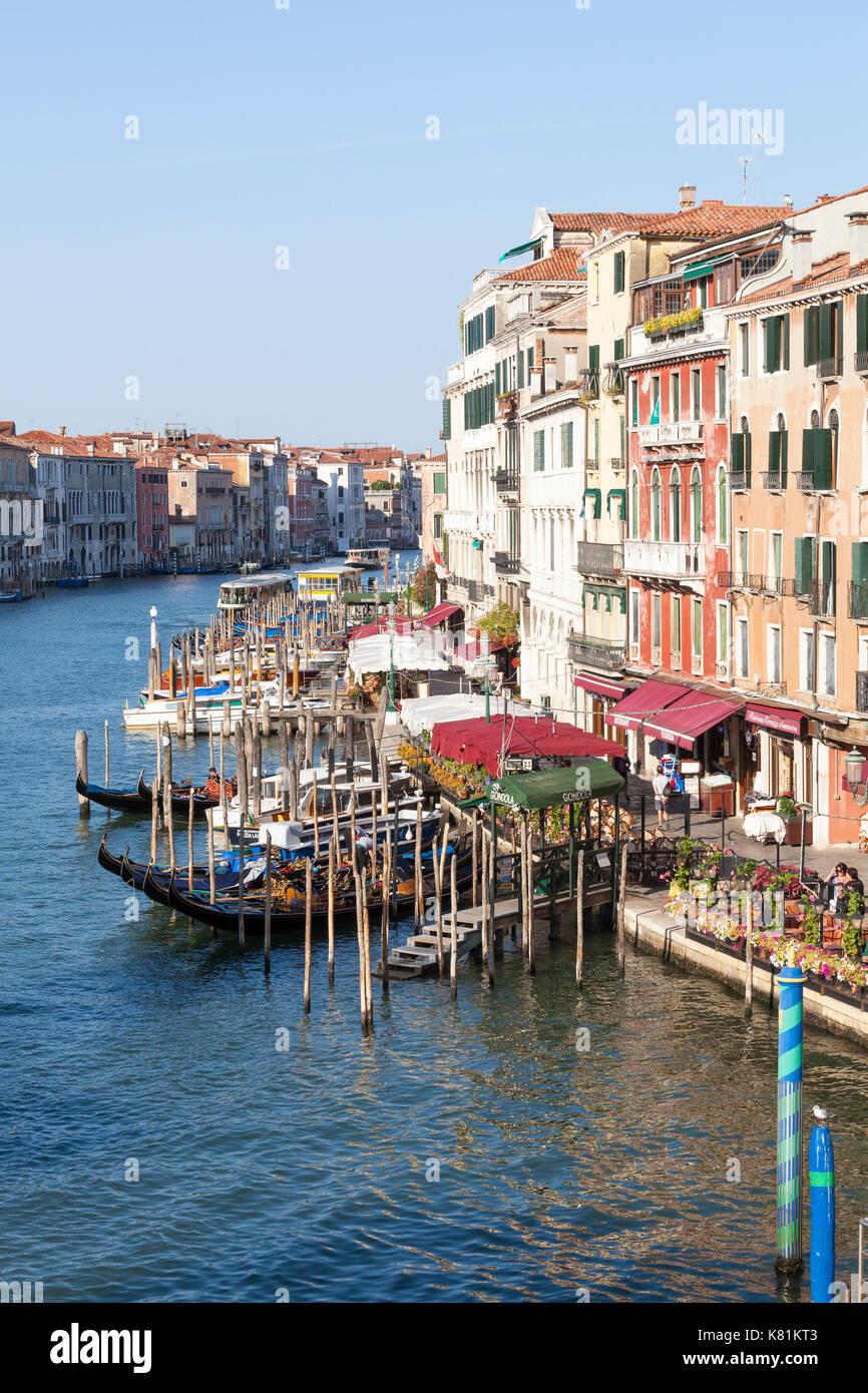 Grand Canal unter Rialto am frühen Morgen goldenes Licht, Venedig, Italien mit goldoliers ihre Gondeln und leere Tabellen anschickt, bei Open-Air-Restaurants Stockbild
